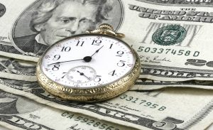 Image of a pocket watch on top of money.