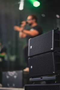 A speaker in the forefront with the lead singer in the background